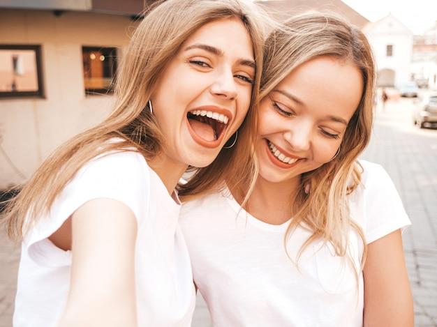 Deux Jeunes Femmes Blondes Hipster Souriant Dans Des Vêtements De T-shirt Blanc D'été. Filles Prenant Des Photos D'autoportrait Selfie Sur Smartphone. Photo gratuit
