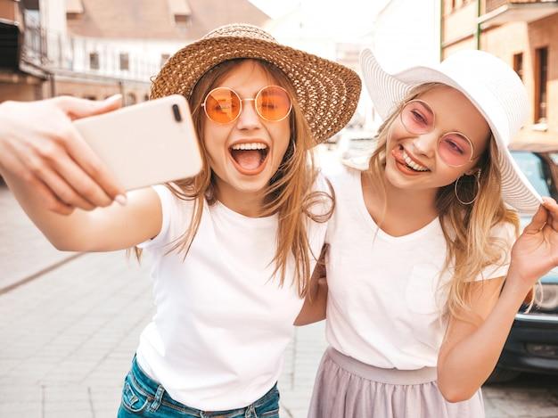 Deux Jeunes Femmes Blondes Hipster Souriantes En T-shirt Blanc D'été. Filles, Prendre, Selfie, Autoportrait, Photos, Sur, Smartphone., Modèles, Poser, Sur, Rue, Arrière-plan., Femme, Montre, Langue, Et, émotions Positives Photo gratuit