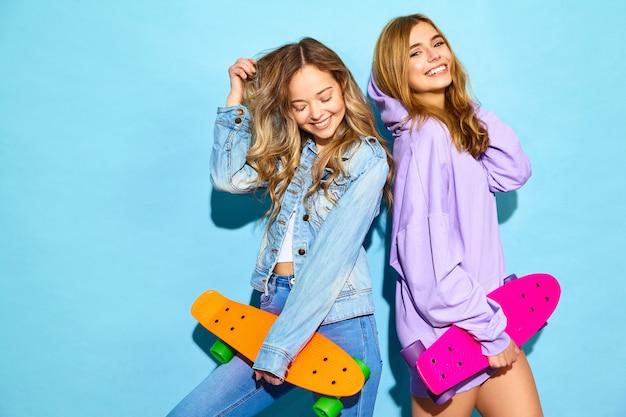 Deux Jeunes Femmes Blondes Souriantes élégantes Avec Des Planches à Roulettes Penny. Femmes En Vêtements De Sport Hipster D'été Posant Près Du Mur Bleu. Modèles Positifs Photo gratuit