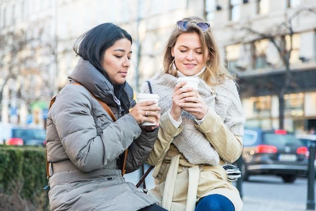 Deux jeunes femmes avec boisson chaude Photo Premium