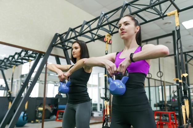 Deux jeunes femmes en bonne santé faisant des exercices avec poids Photo Premium