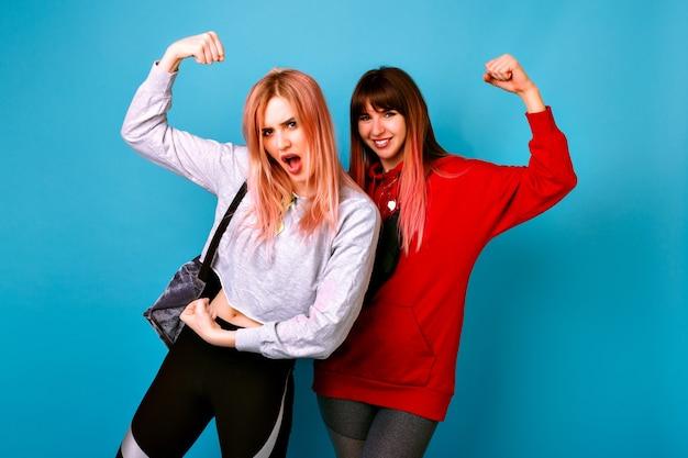 Deux Jeunes Femmes Drôles Assez Hipster Portant Des Tenues Décontractées Lumineuses Sportives, Montrant Les Biceps Et Faisant Des Grimaces, Devenir Fou Ensemble, Mur Bleu Photo gratuit