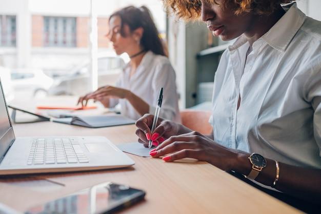 Deux jeunes femmes écrivant un projet dans un studio moderne Photo Premium