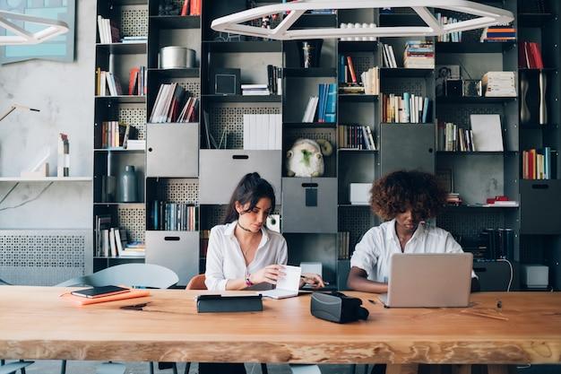 Deux jeunes femmes étudient ensemble dans un bureau de travail moderne Photo Premium