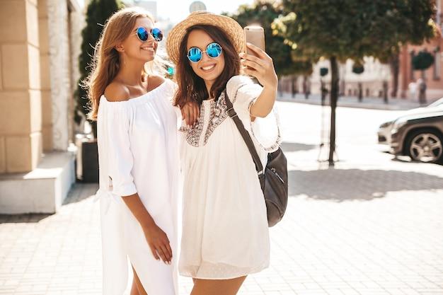 Deux Jeunes Femmes Hippies élégantes Brune Et Blonde Femmes Modèles En Journée Ensoleillée D'été Dans Des Vêtements Blancs Hipster Prenant Des Photos De Selfie Pour Les Médias Sociaux Sur Le Téléphone Femme Positive Photo gratuit