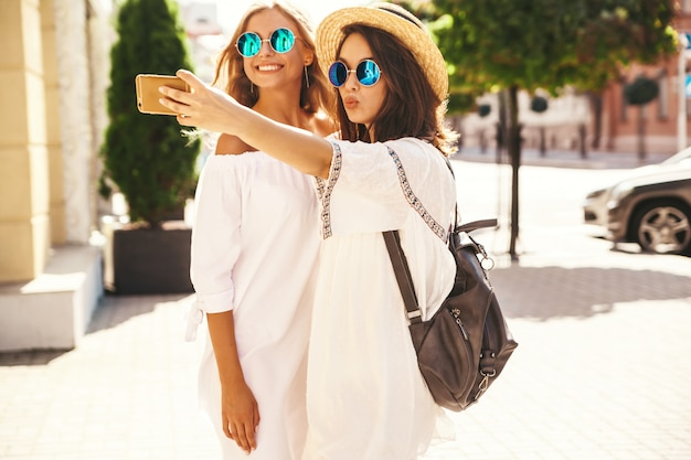 Deux Jeunes Femmes Hippies élégantes Brune Et Blonde Femmes Modèles En Journée Ensoleillée D'été Dans Des Vêtements Blancs Hipster Prenant Des Photos De Selfie Pour Les Médias Sociaux Sur Le Téléphone Photo gratuit