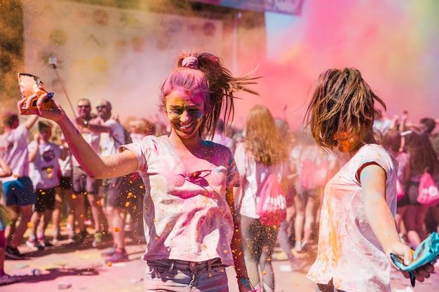 Deux jeunes femmes jouant et appréciant avec des couleurs holi Photo gratuit
