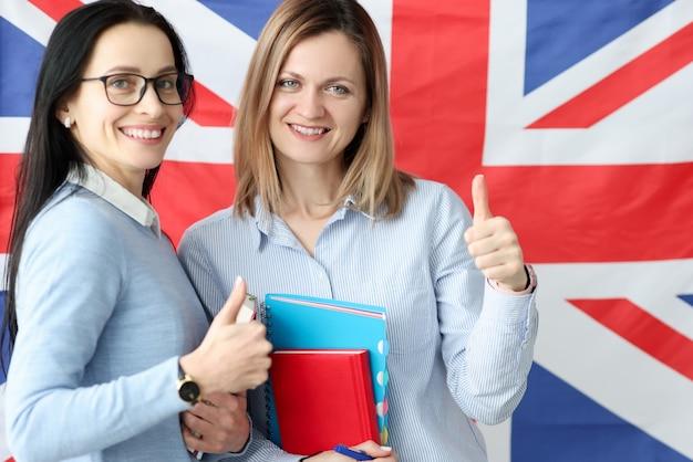 Deux Jeunes Femmes Avec Des Livres En Mains Debout Sur Fond De Drapeau Britannique. Apprentissage De Photo Premium