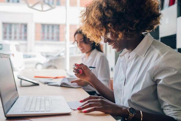 Deux jeunes femmes multiraciales écrivant et travaillant ensemble sur un projet Photo Premium