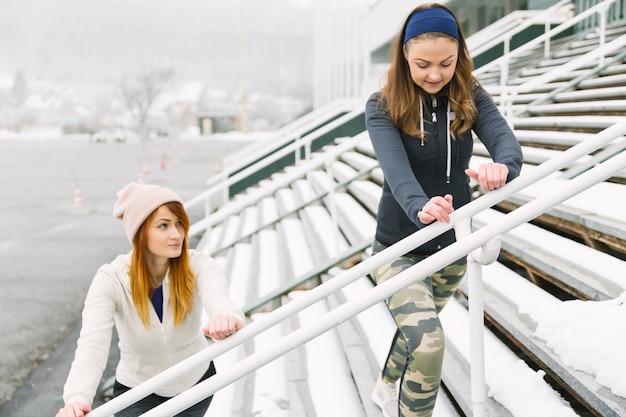 Deux jeunes femmes qui s'étend sur un gradin en hiver Photo gratuit