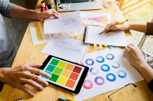 Deux jeunes femmes qui travaillent comme créateurs de mode et dessinent des croquis et obtiennent des conseils en tissu sur un tailleur personnalisé Photo Premium