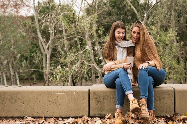 Deux jeunes femmes regardant le téléphone dans le parc Photo gratuit