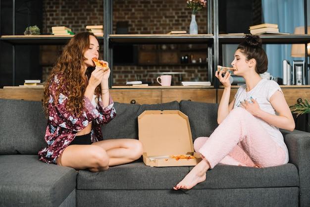 Deux, jeunes femmes, séance, sofa, manger, pizza Photo gratuit