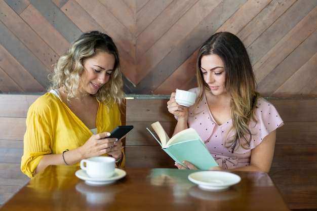 Deux jeunes femmes séduisantes buvant du café et se reposant au café Photo gratuit