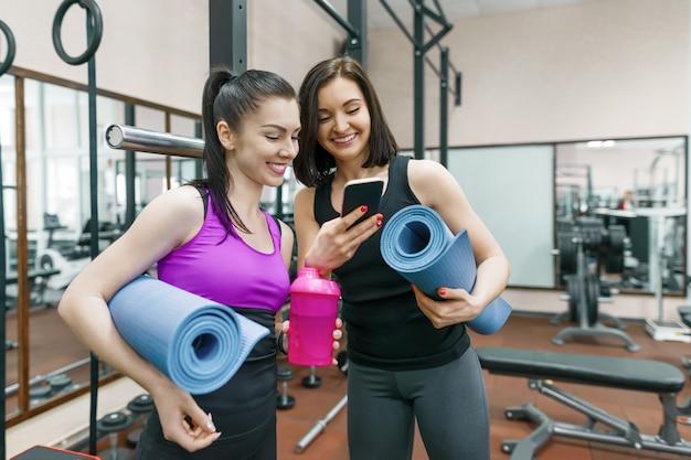 Deux jeunes femmes souriantes de remise en forme, discutant avec des tapis de sport Photo Premium