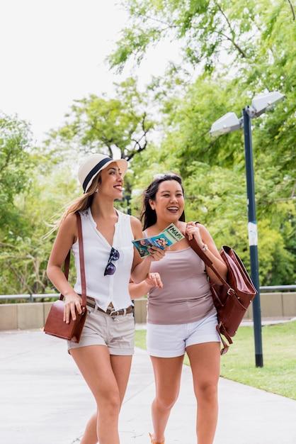Deux jeunes femmes souriantes se promenant dans le parc avec leurs sacs Photo gratuit