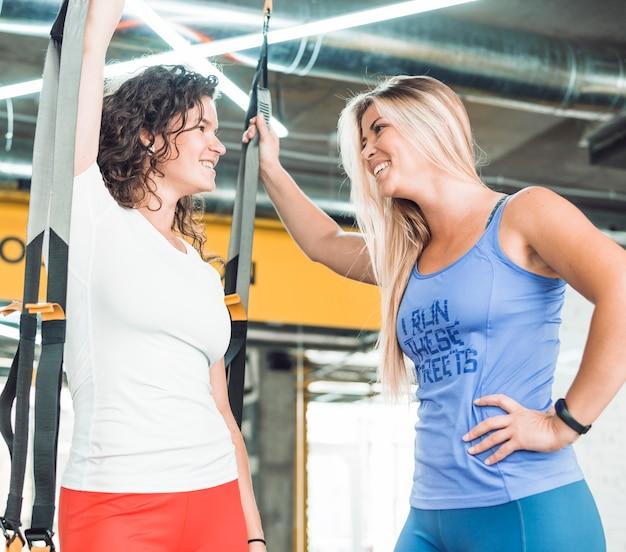 Deux jeunes femmes sportives souriantes se regardant dans la salle de gym Photo gratuit