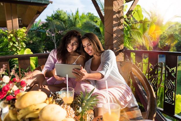 Deux Jeunes Femmes Utilisent Une Tablette Numérique Au Petit-déjeuner Sur La Terrasse Photo Premium