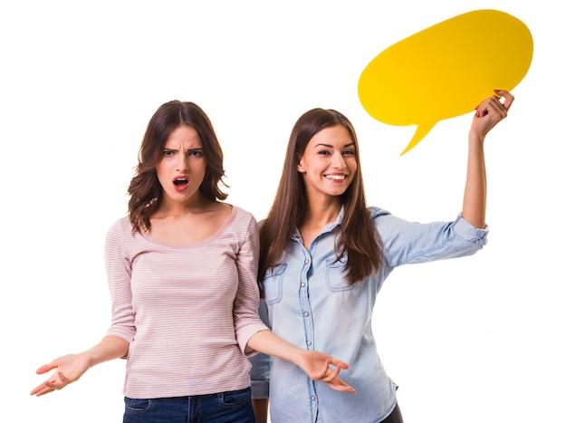 Deux jeunes filles belles, tenant une bulle jaune pour le texte. Photo Premium