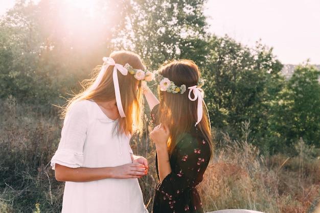 Deux jeunes filles câlin pendant le coucher du soleil sur le terrain avec le concept d'amitié verres à vin Photo Premium