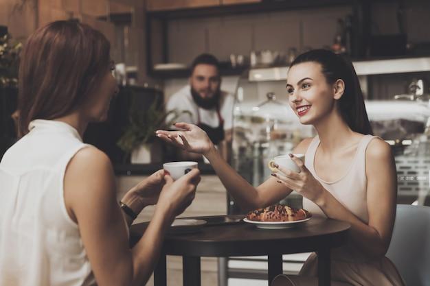 Deux jeunes filles communiquent dans un café à la table Photo Premium