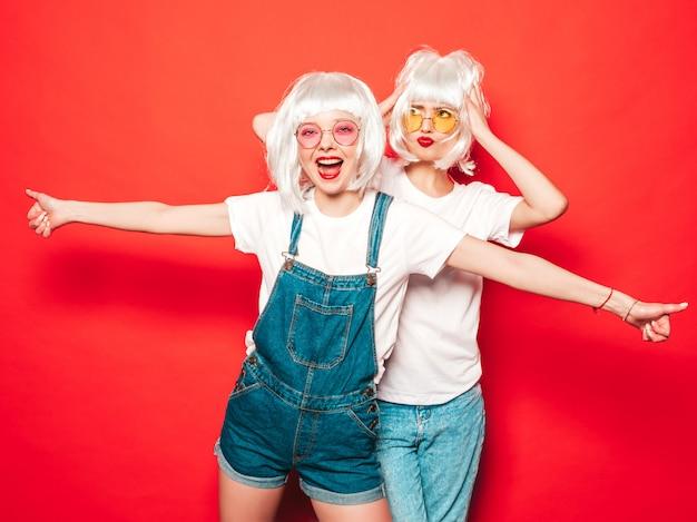Deux Jeunes Filles Sexy Hipster En Perruques Blanches Et Lèvres Rouges. Belles Femmes à La Mode Dans Les Vêtements D'été. Modèles Sans Soucis Posant Près Du Mur Rouge En Studio D'été En Lunettes De Soleil Photo gratuit
