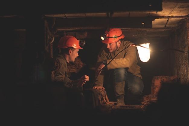 Deux Jeunes Gars Portant Des Vêtements Spéciaux Et Des Casques, Travaillant Dans La Mine Photo Premium