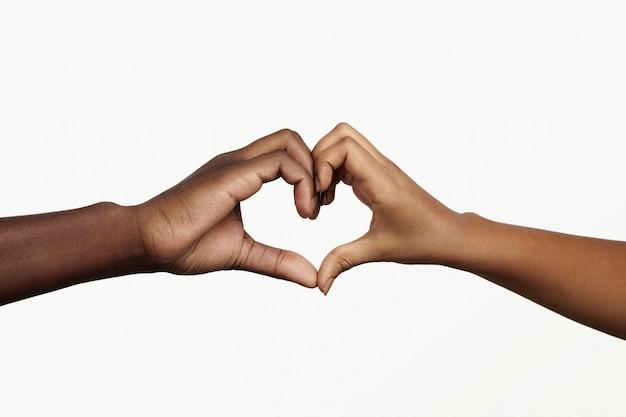 Deux Jeunes Gens à La Peau Sombre Se Tenant La Main En Forme De Coeur, Symbolisant L'amour, La Paix Et L'unité. Photo gratuit