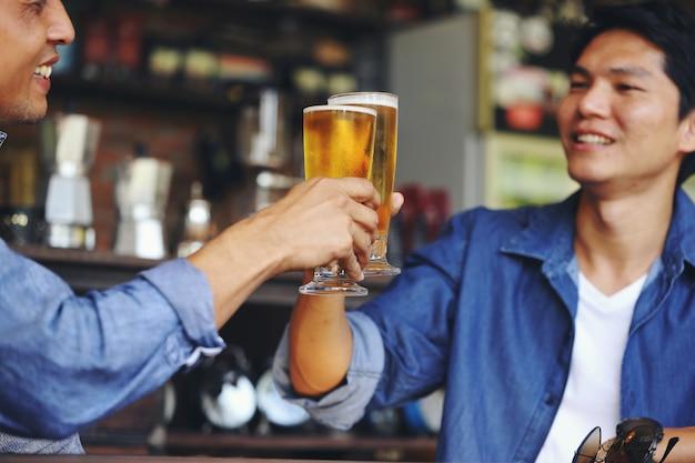 Deux Jeunes Hommes Entrant En Collision Avec Deux Verres De Bière Pour Célébrer Leur Succès. Photo Premium