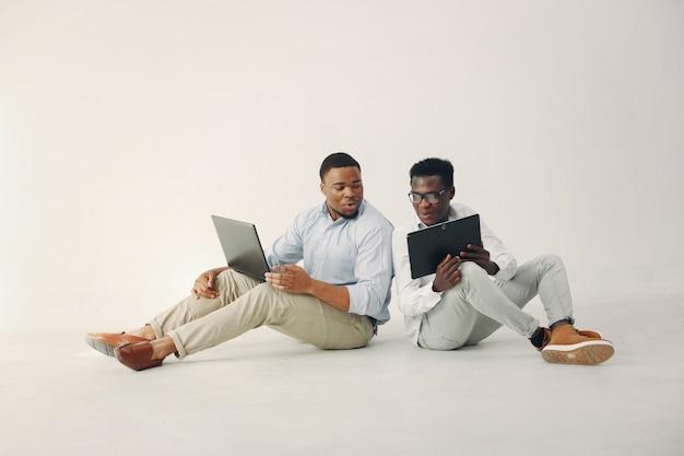 Deux Jeunes Hommes Noirs Travaillant Ensemble Et Utilisent L'ordinateur Portable Photo gratuit