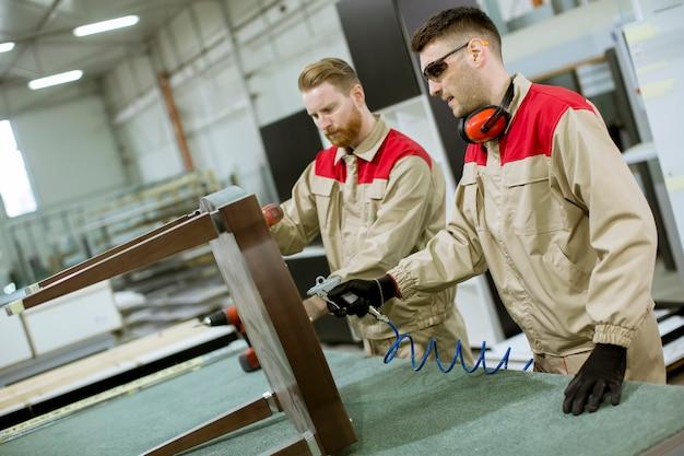 Deux jeunes ouvriers assemblant des meubles dans l'usine Photo Premium