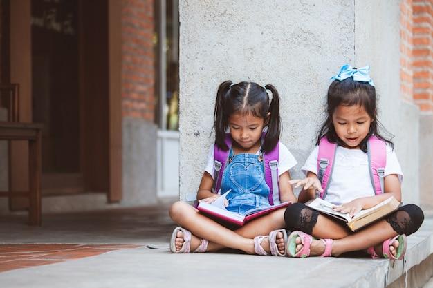 Deux Jolies Filles Asiatiques Lisant Un Livre Ensemble à L'école Avec Plaisir Et Bonheur Photo Premium