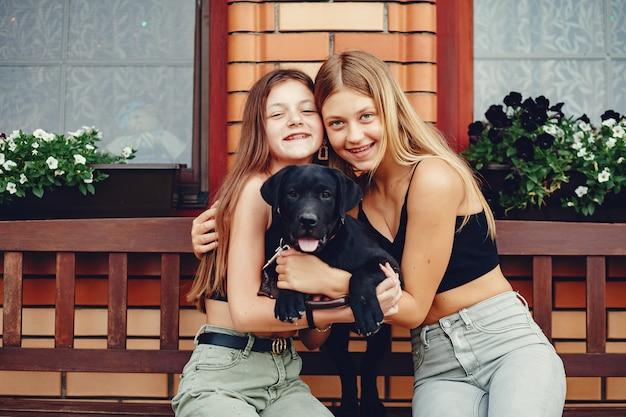 Deux jolies filles dans un parc d'été avec un chien Photo gratuit