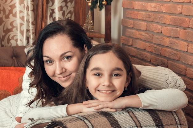 Deux Jolies Filles, Mère Et Fille, S'installant Sur Un Canapé Dans Une Chambre Décorée Pour Noël. Photo Premium