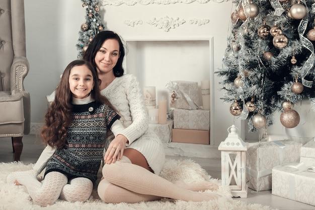 Deux Jolies Filles, Une Mère Et Sa Fille Installées Sur Un Sol Dans Une Chambre Décorée Pour Noël. Photo Premium