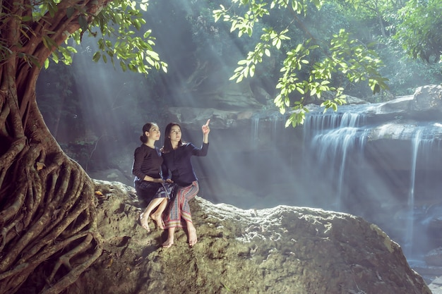 Deux jolies filles se détendre près de la cascade. Photo Premium