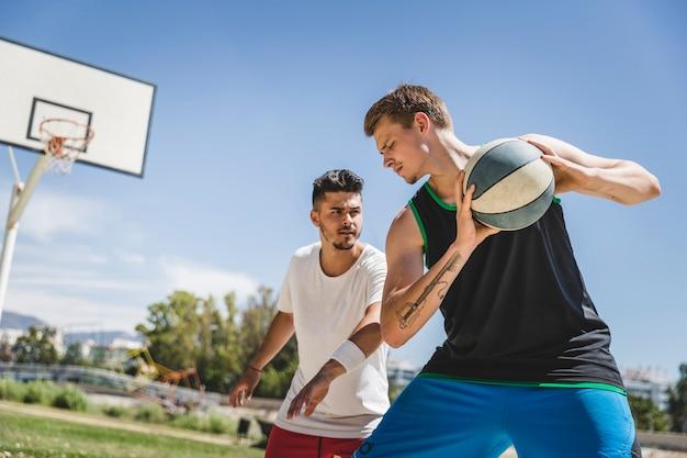 Deux joueurs masculins jouant avec le basketball Photo gratuit