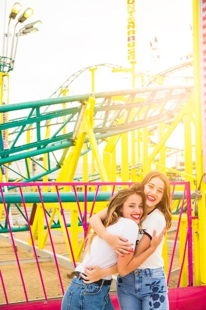 Deux joyeuses amies s'embrassant devant le roller coaster Photo gratuit