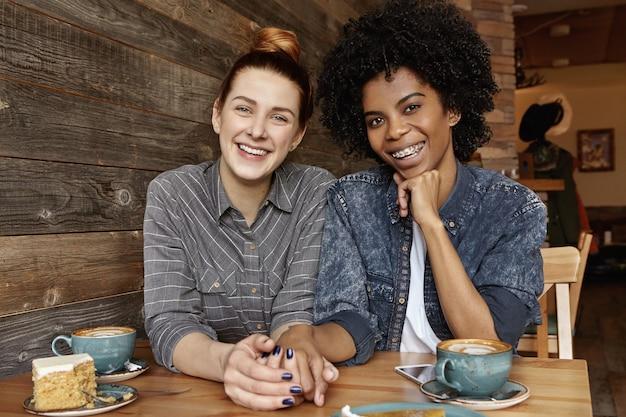 Deux Lesbiennes De Races Différentes S'amusant Ensemble Au Café Photo gratuit