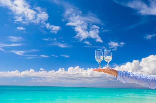 Deux lunettes propres à la main masculine sur fond de ciel bleu Photo Premium