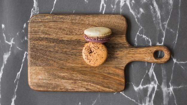 Deux macarons sur une planche à découper en bois sur le fond de marbre Photo gratuit