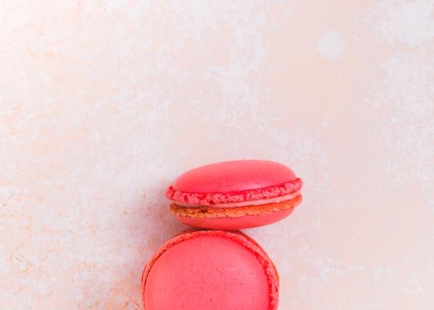 Deux macarons roses sur fond texturé Photo gratuit