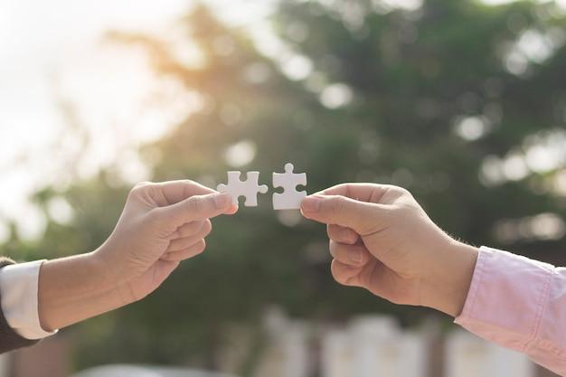 Deux mains d'affaires essayant de connecter une pièce de puzzle couple avec fond de coucher de soleil Photo Premium