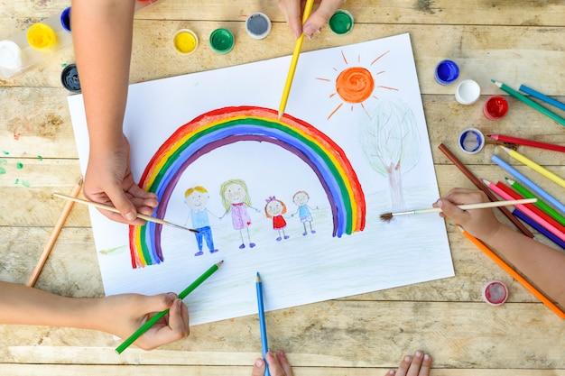Deux mains d'enfants dessinent un dessin avec un pinceau et de la peinture. vue de dessus Photo Premium