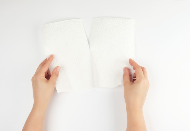 Deux mains féminines tenant une serviette en papier blanc propre pour le visage et le corps Photo Premium