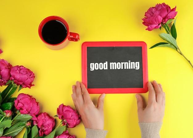 Deux mains féminines tiennent un cadre de craie noire avec les mots bonjour Photo Premium