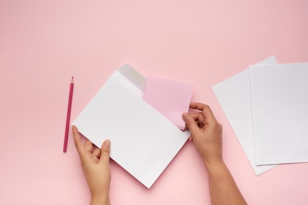 Deux Mains Féminines Tiennent Une Enveloppe De Papier Blanc Sur Une Surface Rose Photo Premium