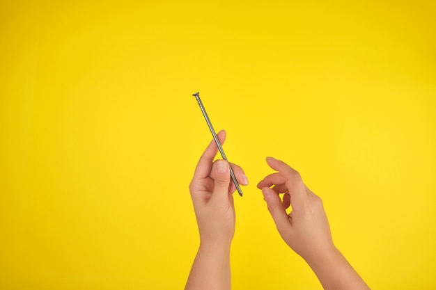 Deux mains féminines tiennent un grand clou de fer, fond jaune, Photo Premium