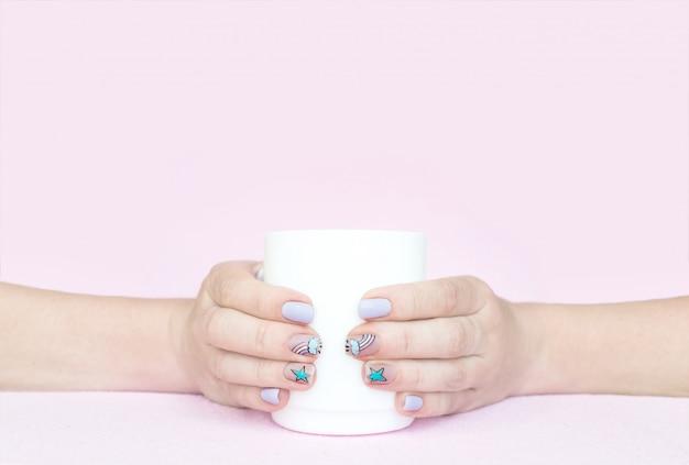 Deux mains féminines tiennent une tasse blanche sur fond rose Photo Premium