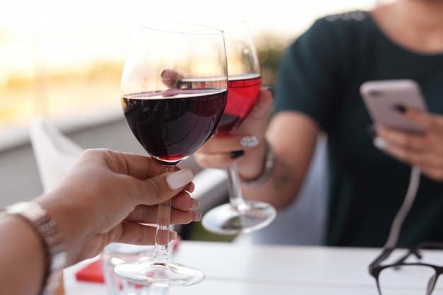 Deux mains d'une fille dans un beau restaurant à une table tenant des lunettes Photo Premium